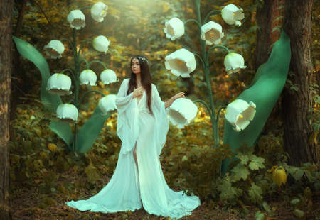 Beautiful fantasy woman princess elf in long white dress walks in fairy forest with large flowers lilies of valley. Queen girl in silver diadem. Silk vintage outfit with wide sleeves. Green trees