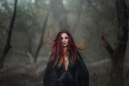 Mysterious fantasy gothic woman dark witch obsessed by evil. Red-haired Girl demon in black dress cape hood. Red hair flutters in wind. Dark dense deep forest background, trees. Scleral lenses on eyes 免版税图像