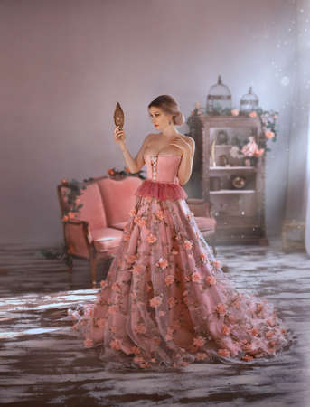 beautiful woman in long medieval pink dress, spring flowers on skirt, looks at herself. Holds in hand vintage mirror. Adult girl queen with big in corset, open chest. Elegant bun hair