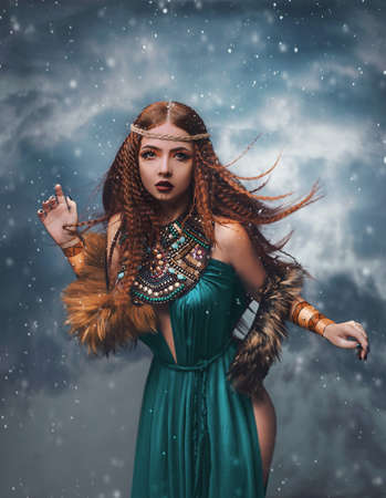 redhead fantasy woman stands in clouds. Fashion model posing in studio background dramatic winter sky, smoke. Elf princess girl. Long red hair flying in wind snow is falling. Blue dress ethnic makeup.