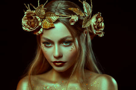Fantasy portrait of woman with golden skin. Girl goddess in wreath, gold roses, accessories. Beautiful face, steel glitter makeup. Artistic photo, black background. Elf fairy princess. Fashion model. Reklamní fotografie