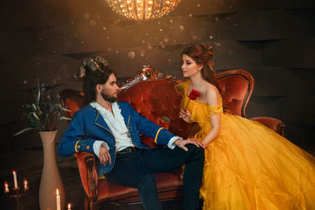 loving couple sits on medieval vintage sofa. Happy beauty woman fantasy princess in yellow dress looks at man prince. guy enchanted beast, horns on head. Blue caftan tailcoat carnival monster costume
