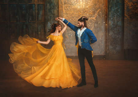 loving couple is dancing at fairy ball. Happy beauty woman fantasy princess in yellow dress and guy is enchanted beast, horns on head Girl whirls in arms of male prince. Man monster carnival costume