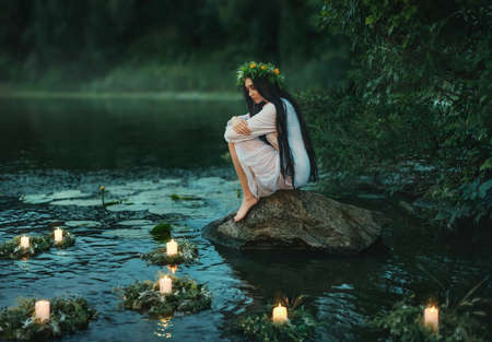 Slavic girl sits on stone on shore lake. Nymph fantasy woman hugs knees. Long black hair. Wreaths of grass, flowers float on water. Candles burning. River dusk forest green tree. Riutal of Divination Standard-Bild