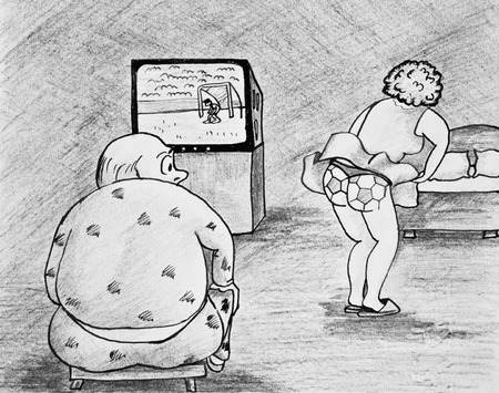 A man watching football on TV. Wife is trying to draw attention to themselves. Stock Photo