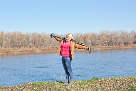 Blondes junges Mädchen am Fluss. Herbst sonniger Tag Standard-Bild
