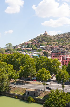 Tbilisi, Georgia-August 07, 2013: Embankment of the Mtkvari river and historic Sololaki district in Tbilisi. Summer day