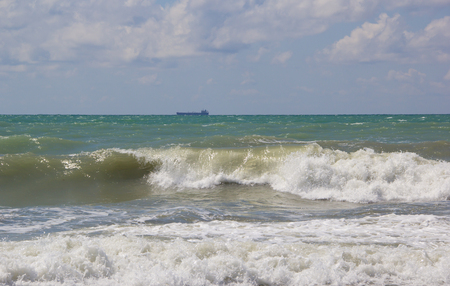 Big waves are rolling on the shore. The ship sails the stormy sea