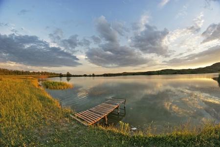 springboard: Lago, puente de madera, puesta de sol Foto de archivo