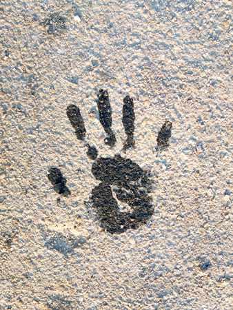 Black Handprint. The imprint of a human hand on the ground. Close-up