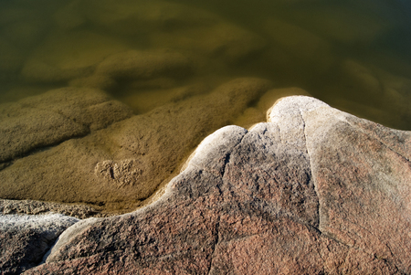 River with a rocky shore. Texture with water and granite. Background texture, close-up.