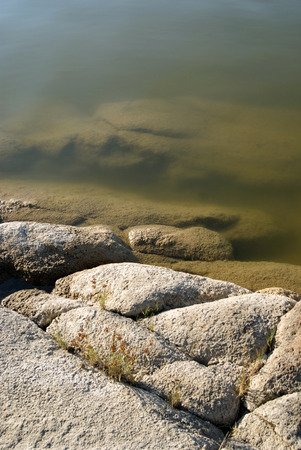 River with a rocky shore. Texture with water and granite. Background texture, close-up