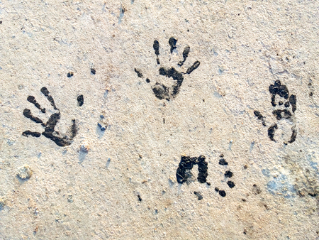 Several Black Handprints. The imprint of a human hand on the ground. Close-up