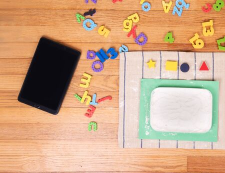 Tablet, colored letters and Flour on floor. Preschool , Home school Concept,  Children at home, preschool and kindergarten. Фото со стока