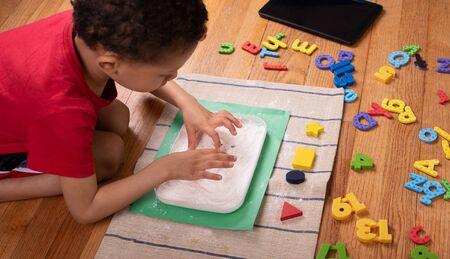 Tablet,  colored letters ,Kid drawing with  Flour on floor. Preschool boy, Home school Concept,  Children at home, preschool and kindergarten.