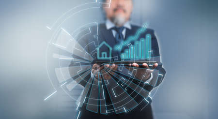 A businessman using digital tablet with house icon, data and business growth on hologram. Futuristic technology style, on blue background.