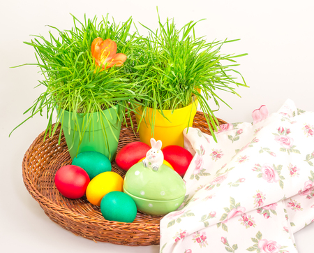 Easter colorful eggs with grass in a pots,with towel and ceramics rabbit
