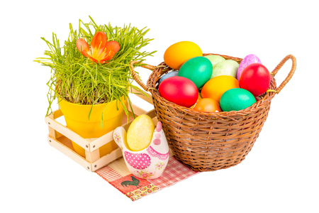 Basket with colorful Easter eggs and pot with green grass on the paper napkin near ceramic chicken Stock Photo