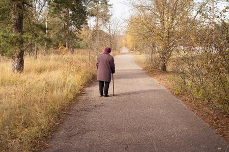 Lonely elderly woman walks in autumn park