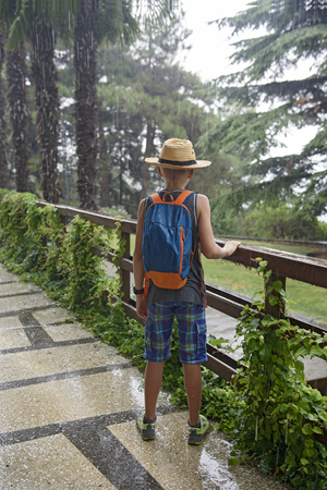 Teenager with a backpack costs under a summer rain.