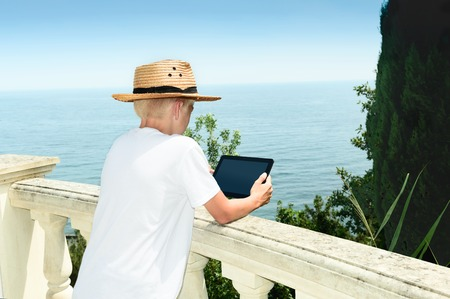 Boy costs against the background of the sea and using the tablet Stock Photo