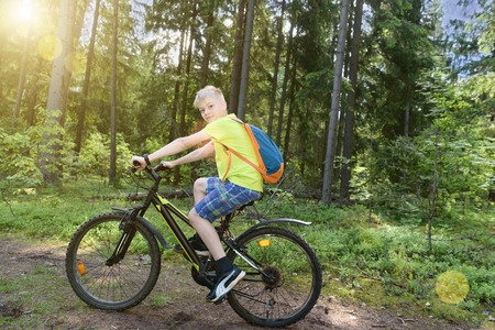 Happy teenager rides a bicycle in pine wood, in sunny day.