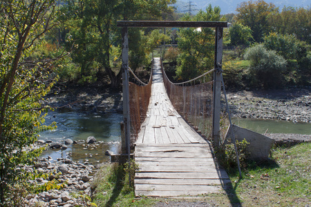 pedestrian bridge: Old wooden bridge over the river. Pedestrian bridge. Wood and Iron Walking Bridge Over Rive