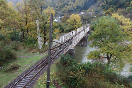 turqoise: The massive railway bridge across the river, Populated place, autumn. Steel supporting structure