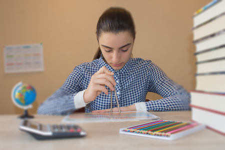 bibliography: Young Girl is working with atlas at the wood table. Education and school concept - little student girl with many books Stock Photo