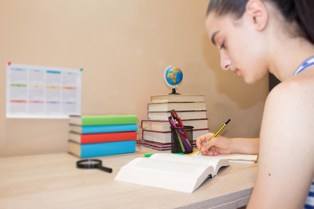 bibliography: Girl doing her homework. Hardback colorful books on wooden table. Education concept - books on the desk in the auditorium.