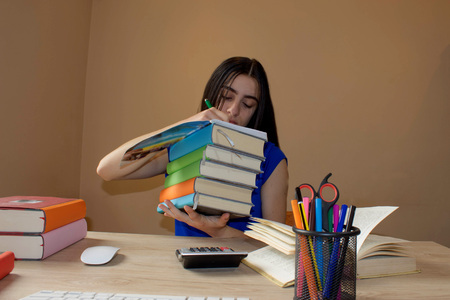 bibliography: Girl doing her homework. Education and school concept - little student girl with many books - books on the desk in the home. Girl studying Stock Photo