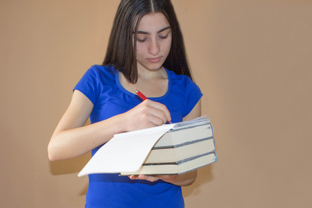 bibliography: Young Girl student with pile of books and notes. Girl writing information she has found in a large book