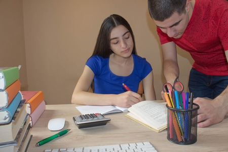 bibliography: Older brother explaining exercise Student sister Working At Desk with writing lesson