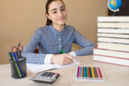 law school: Smiling teenager girl doing homework at the table at home. Education and school concept