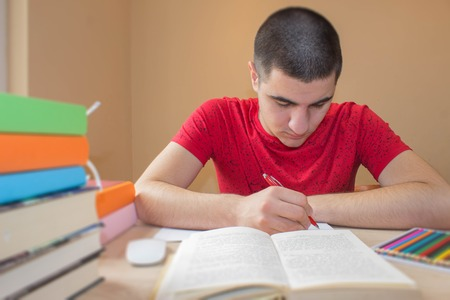 law school: Young student write in notebook between books. Education and school concept - student boy with many books