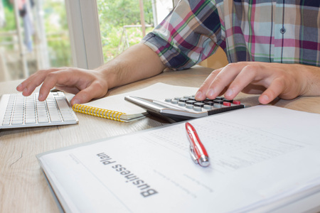 Close up view of bookkeeper or financial inspector hands making report, calculating or checking balance. Home finances, investment, economy, saving money or insurance concept. Business concept Stock Photo