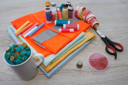 kit de costura: Costura de bodegones: tela de colores. El kit de costura incluye hilos de diferentes colores, dedales y otros accesorios de costura en la mesa de madera. herramientas para coser para pasatiempo Foto de archivo