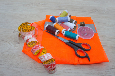 Tools for sewing for hobby set on wooden table background top view. Sewing kit. Thread, needles and cloth Stock Photo