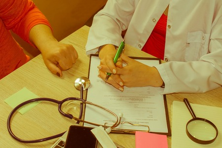 Female doctor holding application form while consulting patient. Medical and Health care concept - Retro color Stock Photo