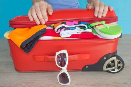 Woman hands packing her red suitcase. Travel and vacations concept. Open travelers bag with clothing, accessories