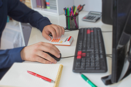 Businessman calculating the financial statements. Close up young man with calculator counting making notes at home. man working on computer in a office