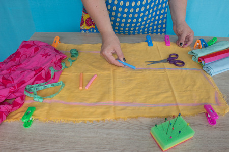 kit de costura: closeup of woman hands sewing yellow cloth outdoors. Womans Hand Sewing Quilt