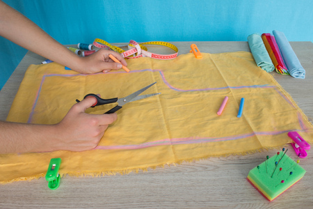 kit de costura: Tailor cutting fabric using large scissors or shears as he follows the chalk markings of the pattern, close up of his hands. Womans Hand Sewing Quilt Foto de archivo