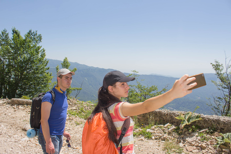 Hikers taking selfie self-portrait photo hiking. Two friends on hike. Friends Taking Selfie at Top in Mountain