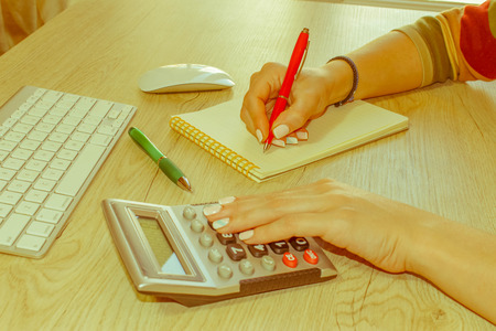 Savings, finances, economy and home concept - Female with calculator, Female holding pens, papers, notes in documents  - Retro color Stock Photo