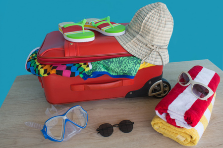 Opened traveler case, Suitcase on table. Red Suitcase with different things prepared for travel Stock Photo