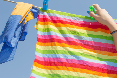 hangers: Clean laundry is hung up by a woman to dry. Woman Hanging up the washing in a outdoor Stock Photo