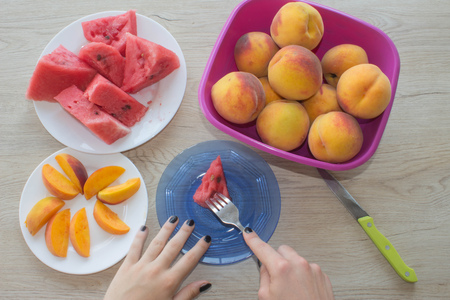 Fresh slices of watermelon and peaches on a plate on the wooden table. Organic Ripe Seedless Watermelon and peaches Cut into Wedges Stock Photo