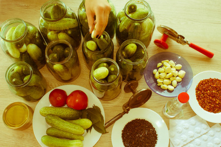 cucumbers: People are preparing in the kitchen. pickling cucumbers, preparation for winter salting. Process of cucumber conservation - Retro color