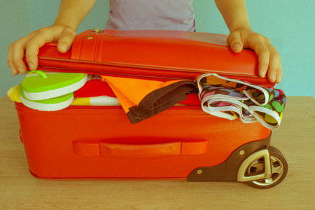 Woman hands putting clothes in suitcase, closeup. Travel and vacations concept. Suitcase with different things prepared for travel - Retro color Stock Photo